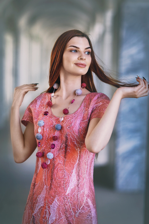 Beautiful stylish girl in a designer pink dress from merino wool, closeup