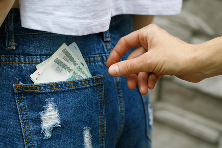 Committing a crime on the street, stealing money from the back of your jeans pocket, close-up Stock Photo