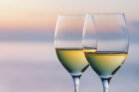 Two glasses of wine against the backdrop of the setting sun with space for text