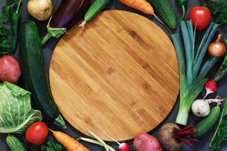 Concept of national cuisine with vegetables from its garden, spread out around an empty cutting board, top view