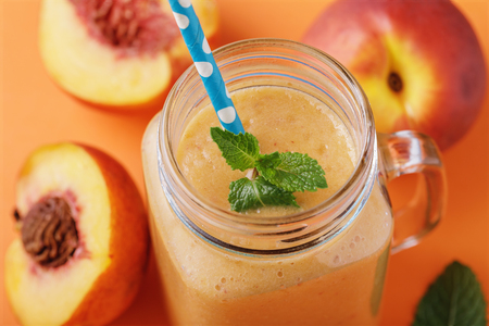 Smoothies made from ripe peaches in a glass jar with mint and fruits on a wooden table, close-up Banque d'images