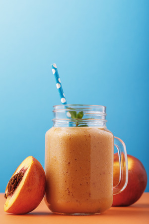 Smoothies made from ripe peaches. Healthy drink in a glass jar on a blue background Stock Photo