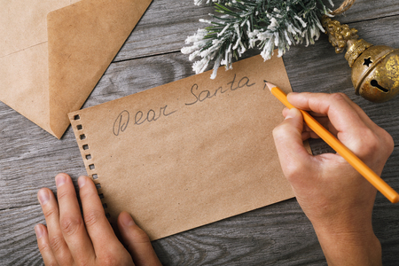 Letter to Santa Claus. Christmas decorations and a sheet of paper with a place for greeting on an old board, top view Stock Photo