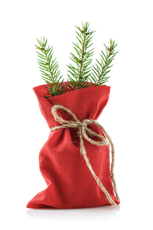 Bag of red color with gifts for new year and fir branches, isolated on white background