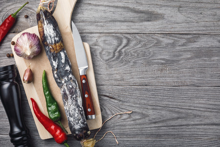 Delicious smoked sausage on a cutting board with pepper and garlic. Top view with copy space