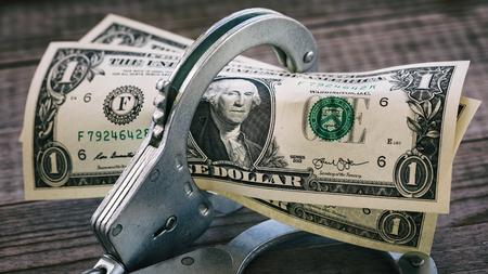 Dollar bills in handcuffs on a wooden table. Concept of limiting the circulation of currency Stok Fotoğraf