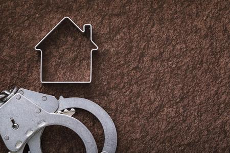 Handschellen und eine Figur in Form eines Hauses auf Steinoberfläche mit Kopierraum. Konzept zu Immobilienbetrug