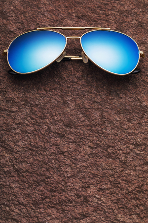 Classic sunglasses on a stone surface with copy space