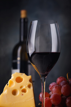 Glass of red wine with cheese and grapes, closeup 免版税图像