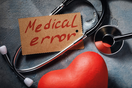 Medical error concept: stethoscope and heart shaped object, close-up