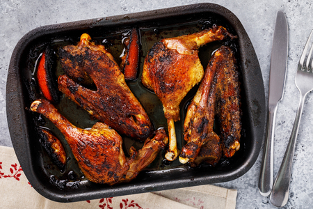 Baked duck with grilled oranges in a baking tray on the table