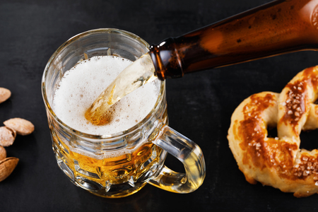 Glass of fresh light beer with salted pretzels and nuts on the table. Process of pouring the drink