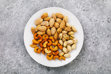 Nuts for beer in a white ceramic plate, top view