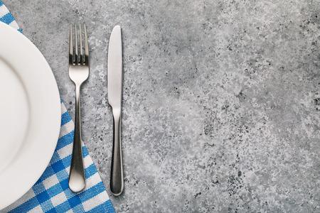 Forchetta, coltello e piatto bianco su un tavolo con trama di cemento, vista dall'alto. Sfondo di cibo