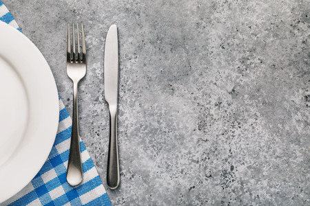 Fork, knife and white plate on a table with texture of concrete, top view. Food background Imagens