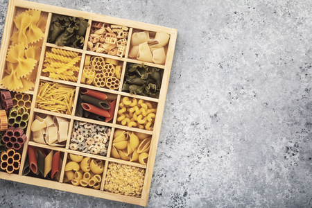 Set of different pasta in a wooden box with copy space, top view
