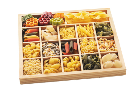 Set of pasta of various shapes and colors in a wooden box, isolated on white background