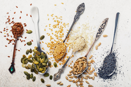 Seeds of pumpkin, flax, sesame, sunflower and poppy in metal spoons on a table, top view close-up Banque d'images