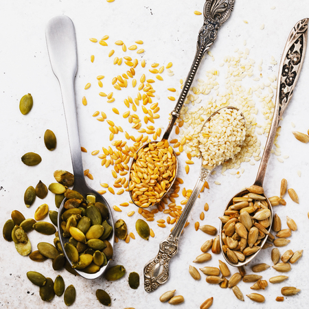 Seeds of a flax, sesame, sunflower and pumpkin in silver spoons on a table, the top view