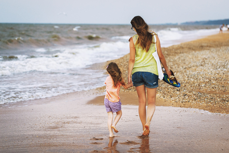 Mom and daughter walk along the seashore in cloudy weather