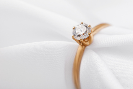 Beautiful gold engagement ring with a diamond on a silk fabric with copy space, close-up