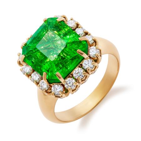 Złoty pierścionek z dużym szmaragdem i diamentami na białym tle