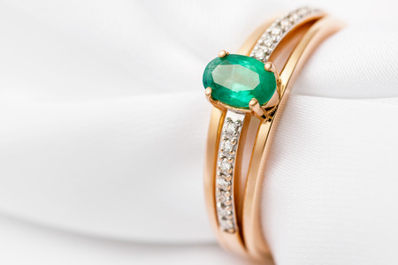 Beautiful golden ring with emerald and cubic zirconias on white silk with copy space