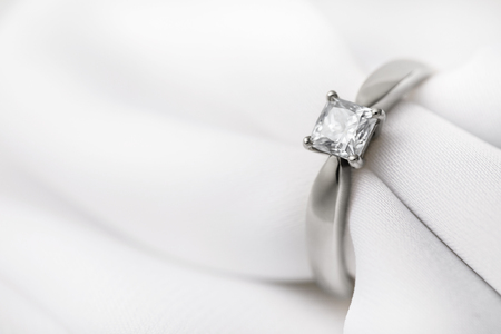 White gold wedding ring with a large diamond on a silk fabric with copy space, close-up