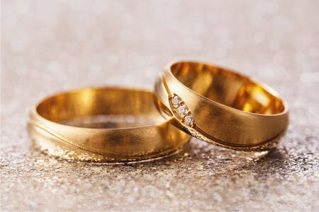 Two wedding rings on abstract background, close-up