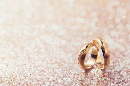 Dos anillos de boda sobre fondo abstracto con espacio de copia