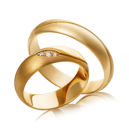 Two gold wedding rings with diamonds isolated on white background. The photo was taken by stacking