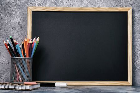A set of various pencils, pens and a chalk board with copy space