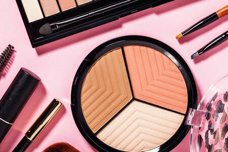 Set of various makeup tools on pink background, top view