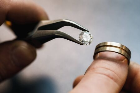 Jeweler tries on a precious stone in a gold blank for the future of the ring, close-up Stock fotó