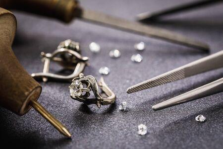 Ohrringe mit einem Stein auf dem Tisch, umgeben von Werkzeugen für die Reparatur von Schmuck Standard-Bild
