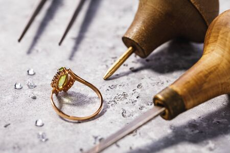 Gold ring with precious stones on the table, surrounded by jewelry repair tools