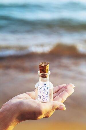 Message in a bottle with the inscription: we will definitely return. Concept with copy space Zdjęcie Seryjne