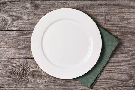 Assiette en céramique vide avec serviette verte sur une table en bois, vue de dessus. Fond de nourriture