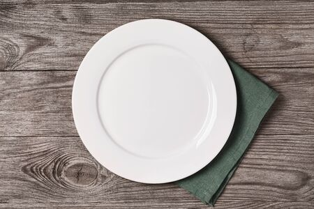 Empty ceramic plate with green napkin on a wooden table, top view. Food background