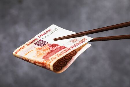 Chinese sticks hold rolled up five thousand rubles.