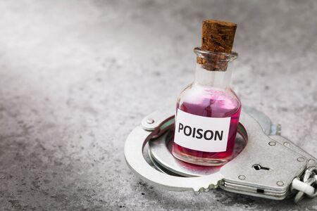 Botella con veneno y esposas sobre una mesa. Foto de archivo
