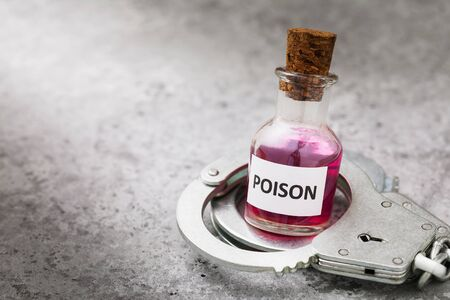 Bottle with poison and handcuffs on a table.