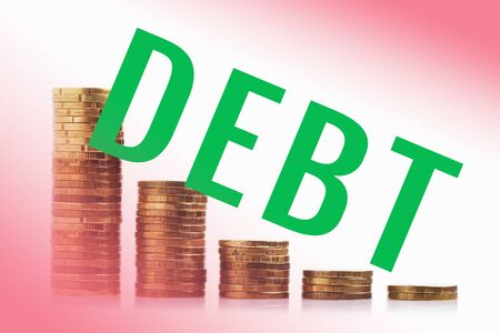 Decrease in credit debt. Piles of coins and the inscription DEBT