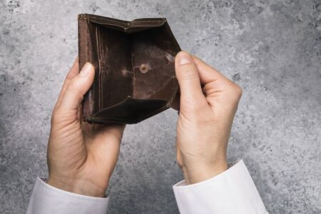 An open empty wallet in the hands of a man. Bankruptcy and lack of money concept