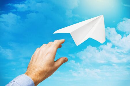 A businessman launched a paper plane into the sky as a symbol of starting in a new business and striving forward