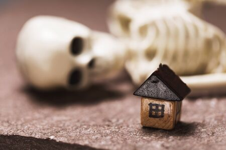Small wooden house and human skeleton close-up. The concept of an unfulfilled dream in buying a home