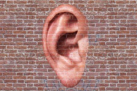 Oreille d'homme sur un fond de mur de briques. Notion d'écoute Banque d'images