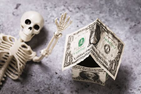 House made of dollars and human skeleton. Concept on the subject of