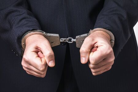 A man in a suit and handcuffs, close-up. Arrest Concept Stock fotó