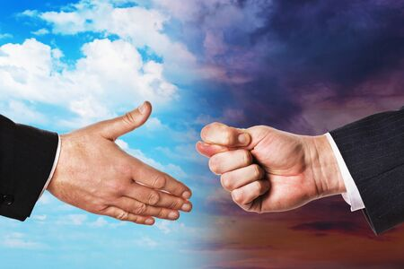 Two hands on a background of the sky with clouds. Concept on offering friendship and refusal